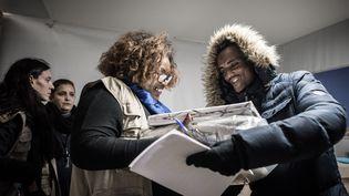 Une travailleuse sociale donne des vêtements à un homme dans un centre pour migrants et réfugiés, à Paris, le 10 novembre 2016. (PHILIPPE LOPEZ / AFP)