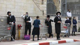 Des Juifs ultra-orthodoxes portent des masques alors qu'ils font la queuedevant une enseigne, àBnei Brak, en Israël, le 6 avril 2020. (MENAHEM KAHANA / AFP)