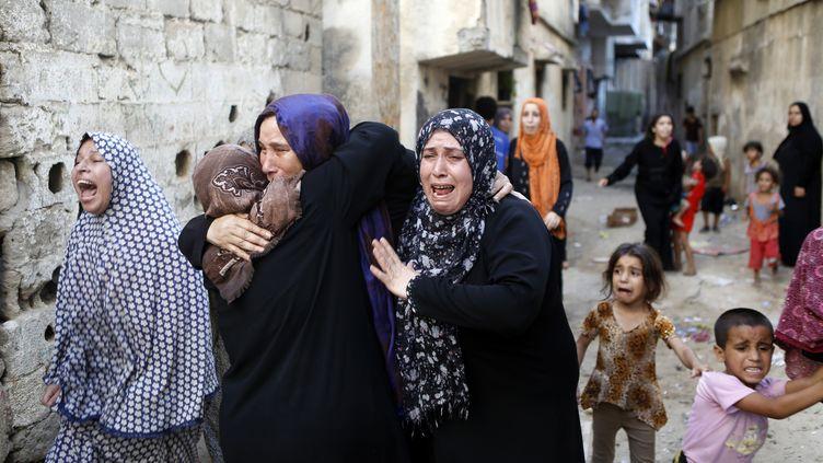 Des femmes palestiniennes pleurent après la mort de quatre garçons, tués le 16 juillet 2014 sur une plage de la bande de Gaza (Israël). (MOHAMMED ABED / AFP)
