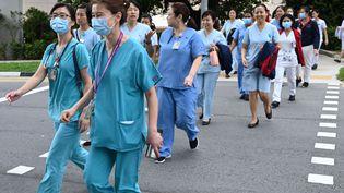 Le personnel médical marche jusqu'au centre national des maladies infectieuses à Singapour le 31 janvier 2020. (ROSLAN RAHMAN / AFP)