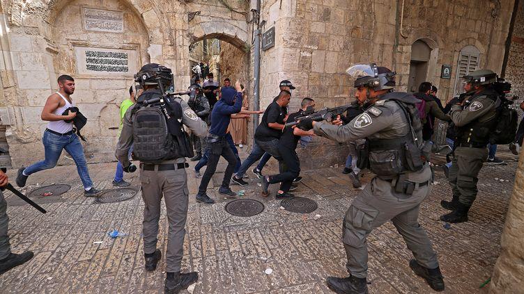 Des manifestants palestiniens fuient les forces de sécurité israéliennes lors d'affrontements dans la vieille ville de Jérusalem, le 10 mai 2021. (EMMANUEL DUNAND / AFP)