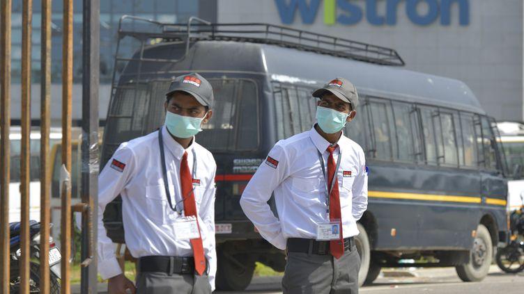 Des vigiles gardent l'entrée de l'usine Wistrom saccagée par des salariés à Bangalore (Inde), le 13 décembre 2020. (MANJUNATH KIRAN / AFP)