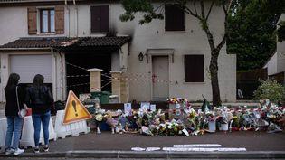 Deux passantes se recueillent devant le domicile de la victime, Chahinez B., brûlée vive par son mari le 4 mai 2021 à Mérignac (Gironde). (STEPHANE DUPRAT / AFP)