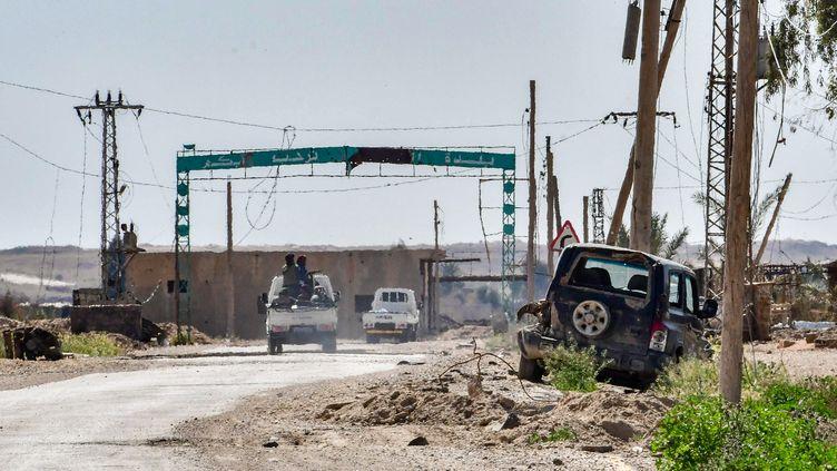 Des véhicules appartenant auxForces démocratiques syriennes circulent à l'entrée deBaghouz(Syrie), le 21 mars 2019. (GIUSEPPE CACACE / AFP)