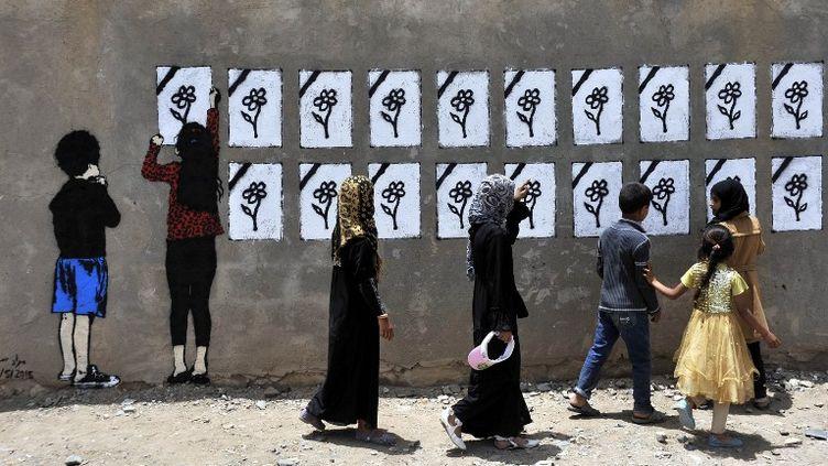 Des personnes regardent des inscriptions à la mémoire des victimes de frappes aériennes, à Sanaa (Yémen), le 18 mai 2015. (MOHAMMED HAMOUD / ANADOLU AGENCY / AFP)