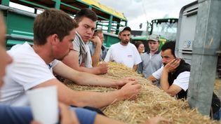Des agriculteurs discutent sur le barrage qu'ils ont installé à proximité de Caen, mercredi 21 juillet. (CHARLY TRIBALLEAU / AFP)