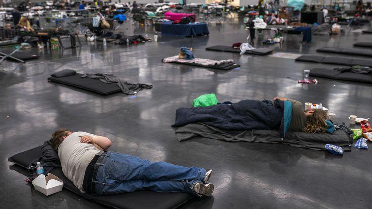 Des habitants de Portland aux Etats-Unis dorment dans un espace climatisé d'une capacité de 300 personnes à l'Oregon Convention Center le 27 juin 2021. (NATHAN HOWARD / GETTY IMAGES NORTH AMERICA)