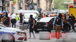 Des policiers à la recherche d'indices sur la zoneoù un colis a explosé, vendredi 24 mai 2019 à Lyon. (PHILIPPE DESMAZES / AFP)