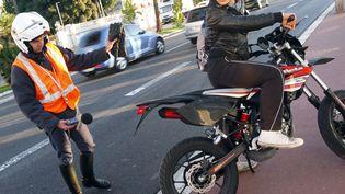 Un policier municipal contrôle le volume sonore d'une moto, le 6 janvier 2010 à Nice, lors d'une opération antibruit des deux-roues. (VALERY HACHE / AFP)