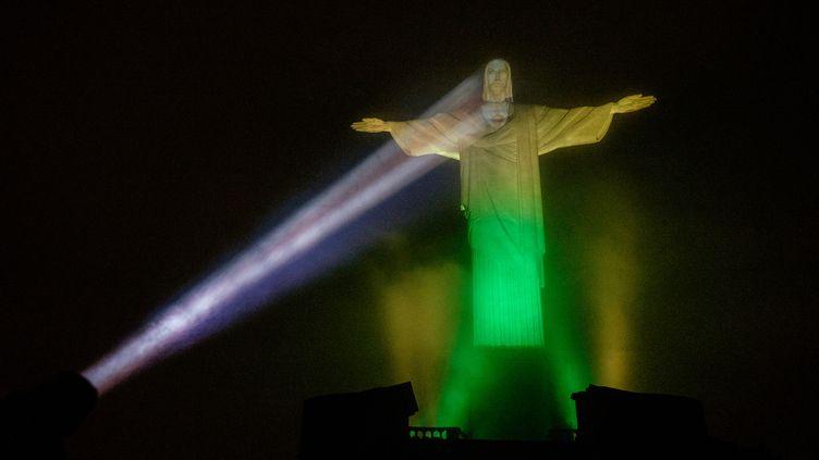 Pour célébrer le J-100, la statue du Christ Rédempteur à Rio de Janeiro s'était parée de jaune et vert, les couleurs du drapeau brésilien (YASUYOSHI CHIBA / AFP)