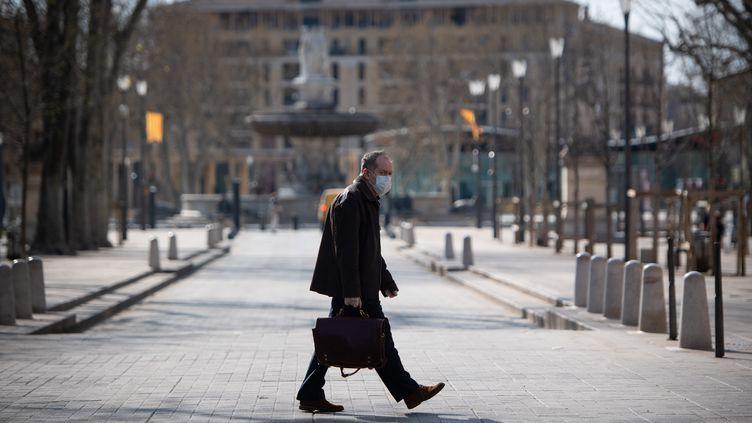 Un passant portant un masque dans les rues d'Aix-en-Provence, le 17 mars 2020. (CLEMENT MAHOUDEAU / AFP)