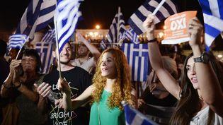 """Des Grecs célèbrent la victoire du """"non"""" au référendum du dimanche 5 juillet 2015. (LOUISA GOULIAMAKI / AFP)"""