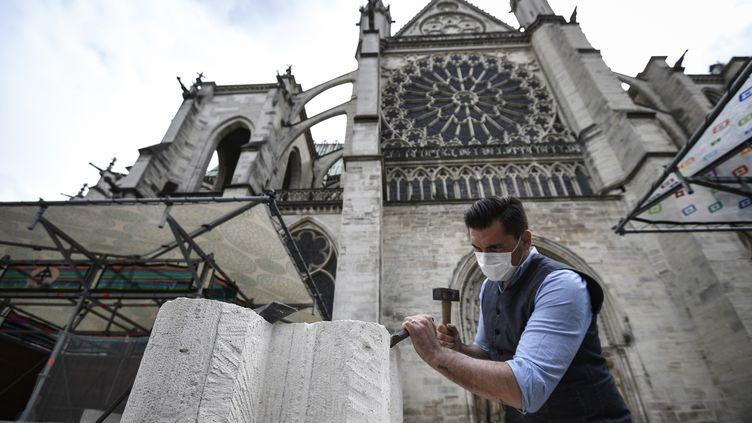 Un tailleur de pierres travaillant à la Basilique Saint Denis, à Saint Denis, le 5 juin 2020 (ANNE-CHRISTINE POUJOULAT / AFP)