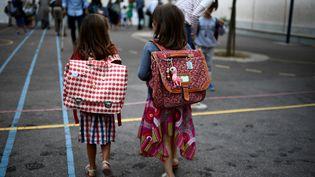 Des enfants entrent dans une cour d'école à Paris pour la rentrée scolaire, le 2 septembre 2019. (MARTIN BUREAU / AFP)