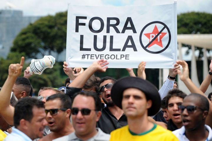 Manifestation contre le gouvernement brésilien à proximité du palais présidentiel le 17 mars 2016, à Brasilia (Brésil). Les manifestants brandissent un panneau où on peut lire «Dehors Lula».   (DRESSA ANHOLETE / AFP)