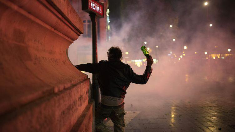 Un homme brandit une bouteille en verre, sur la place de la République, à Paris, en marge du mouvement Nuit Debout, le 23 avril 2016. (ELLIOTT VERDIER / AFP)