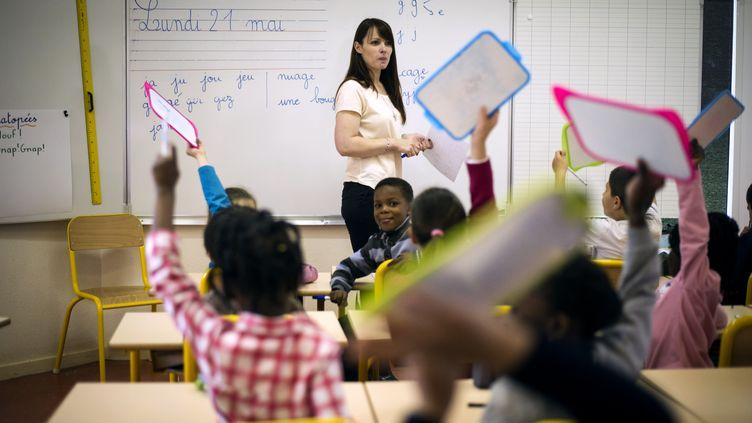 Une enseignante fait cours dans une salle de classe d'une école primaire de Brie-Comte-Robert (Seine-et-Marne), le 21 mai 2012. (FRED DUFOUR / AFP)