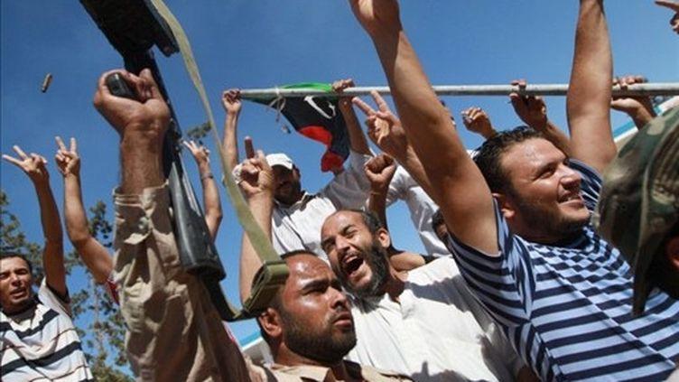 Des insurgés libyens fêtent leur entrée dans la ville de Bir Terfas le 13 août dernier. (MARC HOFER / AFP)