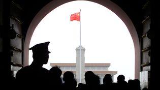Un officier de police chinois surveille la foule qui franchit la porte nord de la place Tiananmen, à Pékin, alors que le drapeau national flotte devant le mausolée de Mao Zedong, le 13 avril 2000. (STEPHEN SHAVER / AFP)