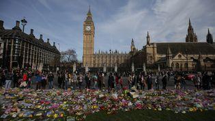 Des fleurs sont déposéesdevant le Parlement britannique en hommage aux victimes de l'attentat qui a touché Londres (Royaume-Uni), le 22 mars 2017. (DANIEL LEAL-OLIVAS / AFP)