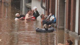 Des habitants évacuent les maisons inondées à Liège en Belgique, le 15 juillet 2021. (BRUNO FAHY / BELGA MAG / AFP)