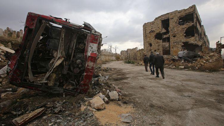 Des Syriens marchent le long d'une rue détruite à Alep, samedi 17 décembre. (YOUSSEF KARWASHAN / AFP)
