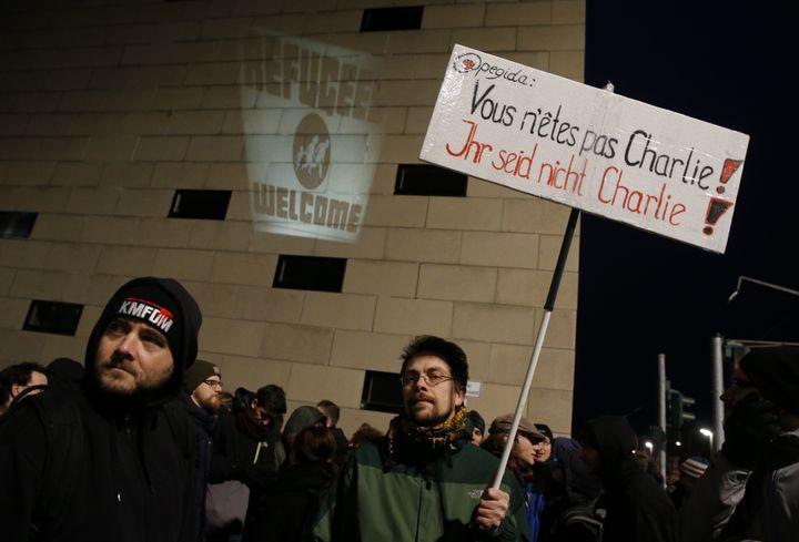"""Un manifestant antiraciste tient un panneau contre la récupération du slogan """"Je suis Charlie"""" par les manifestants anti-islam de Pegida, le 12 janvier 2015, à Dresde (Allemagne). (FABRIZIO BENSCH / REUTERS)"""