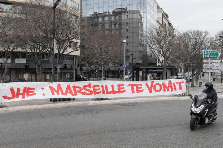 Un conducteur observe une bannière déployée par des supporters de l'OM visant le président du club Jacques-Henry Eyraud, à Marseille, le 30 janvier 2021. (NICOLAS TUCAT / AFP)