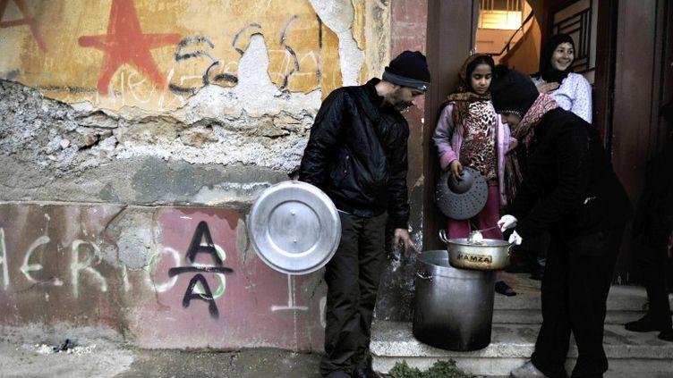 Une membre d'une association sert de la soupe à une famille pauvre à Athènes (Grèce), le 6 février 2012. (LOUISA GOULIAMAKI / AFP)