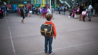 Un écolier dans sa cour d'école, à Paris (illustration). (MARTIN BUREAU / AFP)