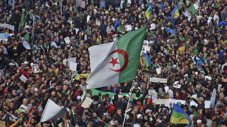 Des manifestants algériens brandissent le drapeau lors d'une manifestation anti-gouvernementale à Alger, le 21 février 2020. (RYAD KRAMDI / AFP)