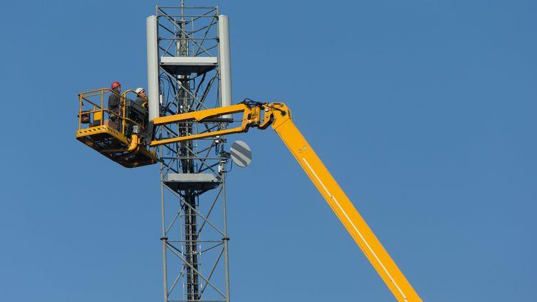 Des techniciens installent une antenne-relais à Bordeaux (Gironde), le 13 mars 2014. (SERGE POUZET / SIPA)