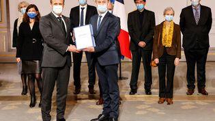 Emmanuel Macron (à g.) et l'historien Vincent Duclert (à dr.), lors de la remise du rapport sur le rôle de la France dans le génocide du Rwanda, le 26 mars 2021, à l'Elysée. (LUDOVIC MARIN / AFP)