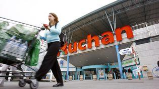 Une femme sort d'un supermarché Auchan avec son chariot, à Villetaneuse (Seine-Saint-Denis). (FRED DUFOUR / AFP)