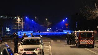 Des policiers patrouillent dans une rue suite à des émeutes et après que plusieurs voitures aient été incendiées dans le quartier de Parilly à Bron, près de la ville de Lyon, le 6 mars 2021. (OLIVIER CHASSIGNOLE / AFP)