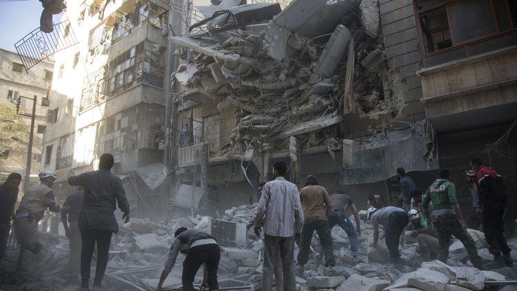 Des civils syriens après un bombardement dans un quartier rebelle de la ville d'Alep (Syrie), le 27 septembre 2016. (KARAM AL-MASRI / AFP)