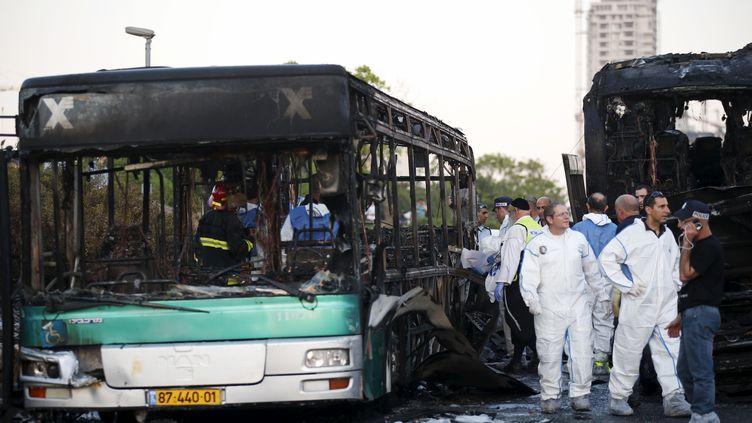 Les secours s'affairent autour des bus calcinés par une explosion, lundi 18 avril à Jérusalem (Israël). (RONEN ZVULUN / REUTERS)