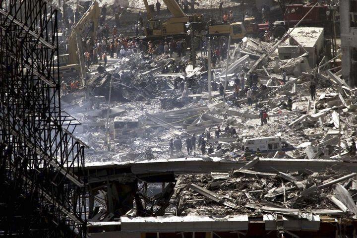Des équipes de secours tentent de retrouver des survivants dans les décombres du World Trade Center, à New York (Etats-Unis), au lendemain des attaques terroristes du 11 septembre 2001. (JIM BOURG / REUTERS)