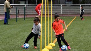 Des jeunes filles participent à une session d'entraînement supervisée par la première école municipale de football, en France. (JEAN-PIERRE CLATOT / AFP)