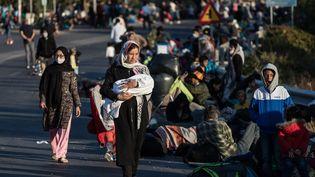 Des demandeurs d'asile rassemblés sur le bord d'une route, sans abri, après l'incendie qui a ravagé le camp de Moria, sur l'île grecque de Lesbos. (KOSTIS NTANTAMIS / SPUTNIK)