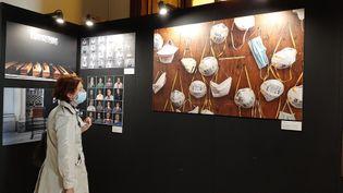 Une visiteuse masquée observe une photographie de la nouvelle normalité: les masques (BRUCE DE GALZAIN / RADIO FRANCE)