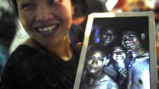 Une mère de famille montre les premières images des12 enfants et de leur entraîneur de football,retrouvés vivants après neuf jours passés dans une grotte du nord de la Thaïlande, le 2 juillet 2018. (LILLIAN SUWANRUMPHA / AFP)