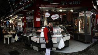 Un boucher du marché de Thessalonique (Grèce), le 11 novembre 2020. (KONSTANTINOS TSAKALIDIS / SOOC / AFP)