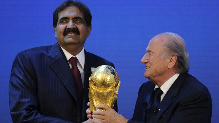 L'Emir du Qatar Sheikh Hamad bin Khalifa Al-Thani (à gauche) reçoit le trophée de la Coupe du monde des mains du président de la Fifa, Joseph Blatter (le 2 décembre 2010). (PHILIPPE DESMAZES / AFP)