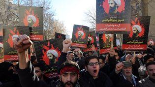 Des Iraniensbrandissent des portraits du cheikh Nimr Al-Nimr lors d'une manifestation devant l'ambassade d'Arabie saoudite à Téhéran (Iran), le 3 janvier 2016. (ATTA KENARE / AFP)