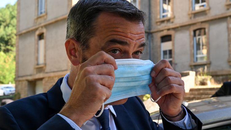Olivier Véran enfile un masque, le 21 août 2020, lors d'un déplacement à Florac (Lozère). (PASCAL GUYOT / AFP)