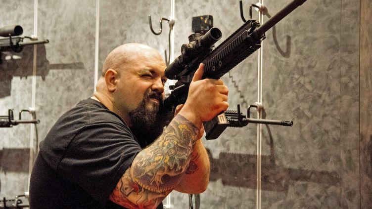 Un homme brandit une arme semi-automatique lors d'un rendez-vous annuel de la National Rifle Association, le lobby des armes américain, le 14 avril 2012 dans le Missouri. (KAREN BLEIER / AFP)