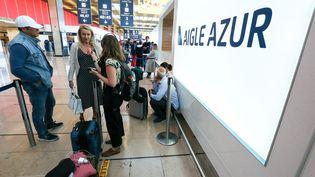 Des passagers attendent devant un comptoir vide d'Aigle Azur, le 6 septembre 2019, à l'aéroport d'Orly. (MICHEL STOUPAK / NURPHOTO / AFP)