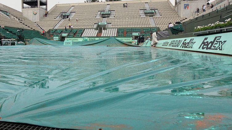 Le court Philippe-Chatrier, protégé par une bâche, en raison de la pluie qui s'est abattue sur Roland-Garros, mercredi 30 mai 2012. (JACQUES DEMARTHON / AFP)