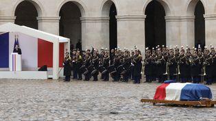 Emmanuel Macron (à gauche) rend hommage à Arnaud Beltrame devant le cercueil du gendarme, mercredi 28 mars 2018 dans la cour de l'hôtel des Invalides, à Paris. (LUDOVIC MARIN / AFP)